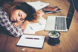 Foto van een vrouw die op haar armen in slaap is gevallen bij haar werkplek. Voor haar liggen papieren en een laptop