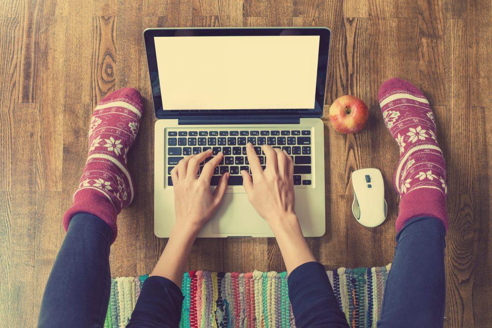 Student aan het werk op de grond achter een laptop